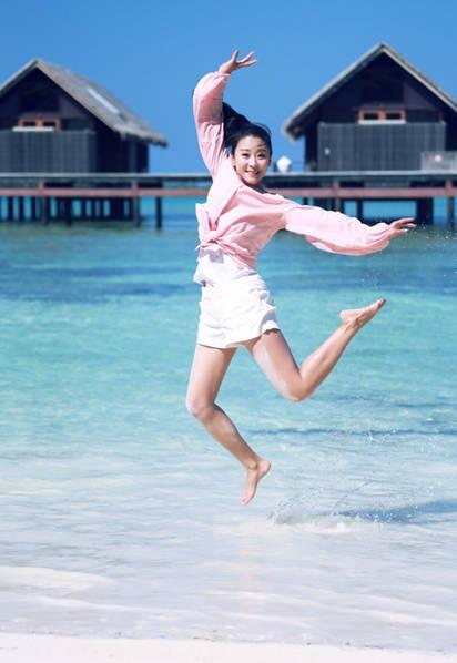"""""""照片中苗圃穿着粉色上衣白色短裤,在沙滩上跳跃,大秀美腿,十分活泼."""