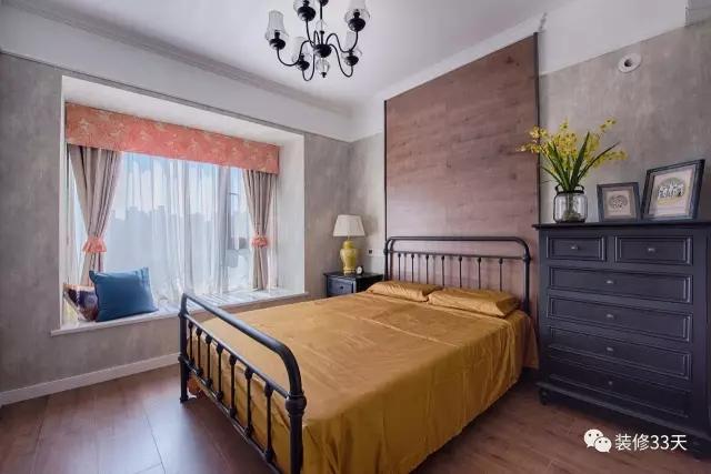 两边饰以黑色铁件,与黑色吊灯相呼应,舒适的飘窗设计成卧室的休闲区
