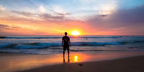 在海边看日落的人图片